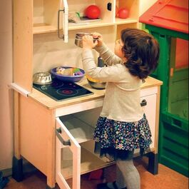 Girl playing inside with kids' kitchen.