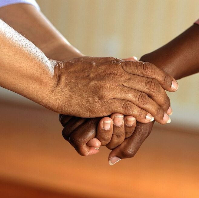 Two people clasping hands after helping each other.